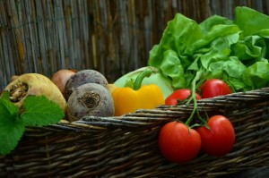 fresh tomatoes, peppers, and other vegetables in a basket