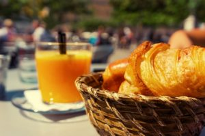 patio table with orange juice and croissants
