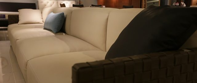 A beige couch with dark accent pillows in a dimly lit living room.