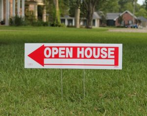 An Open House sign sticking in the grassy lawn of a suburban home.