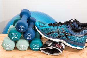 six dumbbells stacked on a wooden surface with a running shoe and glove beside it along with a workout ball in the background.