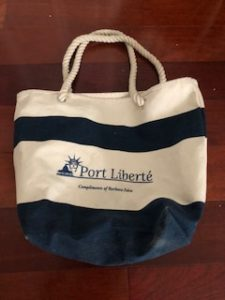 blue and white tote bag with port liberte logo laying on a hardwood surface.