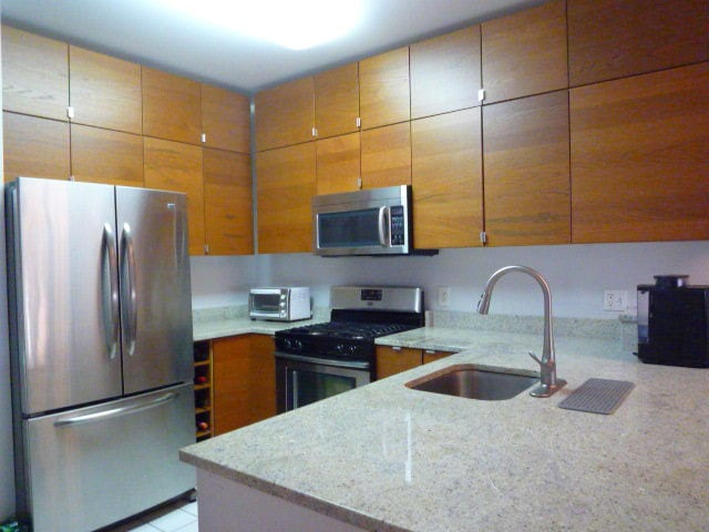 A kitchen with wood cabinets, stainless steel appliances, and a large cooking island.